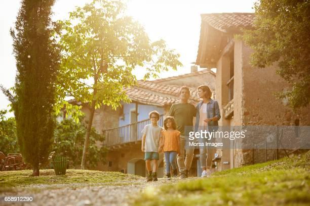 family walking on footpath against houses - cena não urbana imagens e fotografias de stock