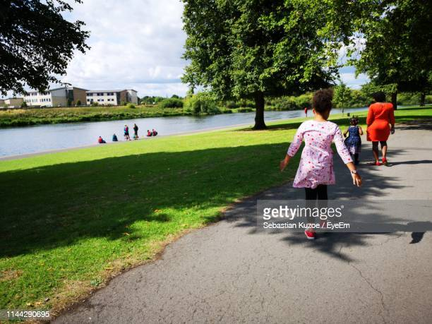 family walking on footpath in city - nottingham stock photos and pictures