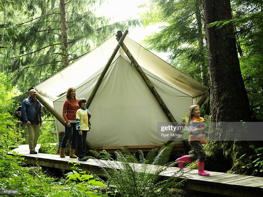 Family walking on pathway next to tent.  Stock Photo & Family Walking On Pathway Next To Tent Stock Photo | Getty Images