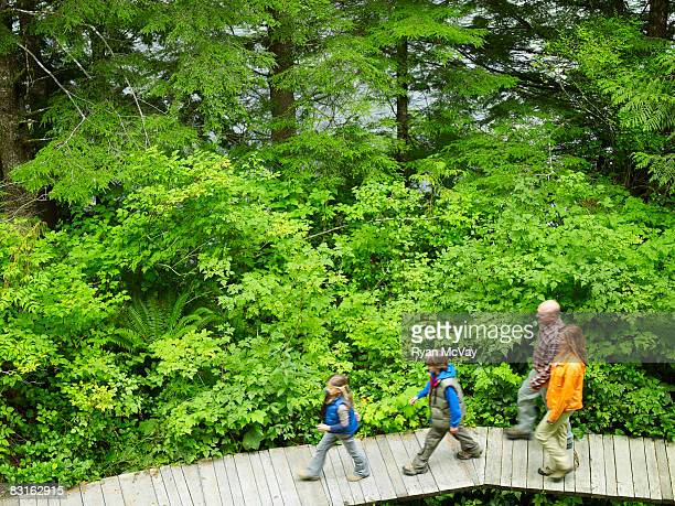 Family walking on pathway through forest.