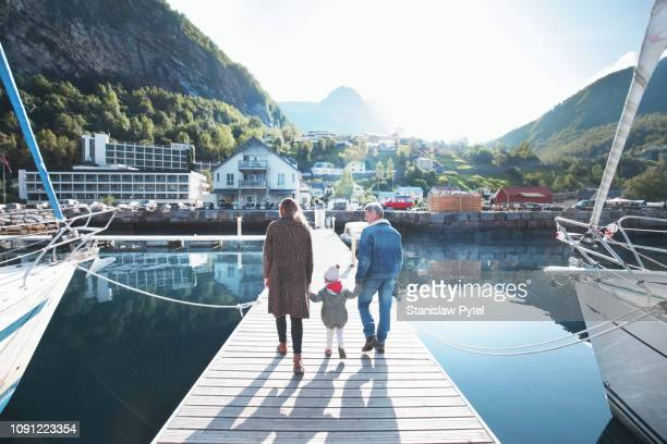 Family walking on pier at sunny day