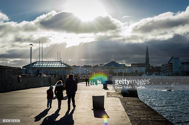 Family Walking On Promenade Against Cloudy Sky At Sunny Day