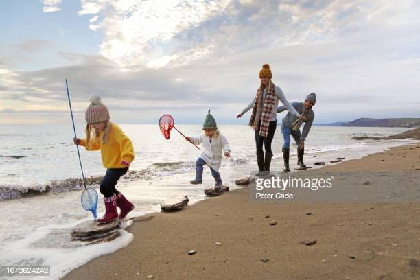 family walking on stepping stones on beach - yellow coat stock pictures, royalty-free photos & images