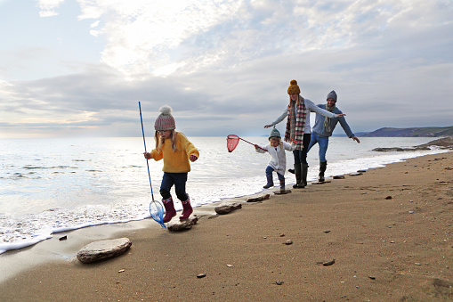 Family walking on stepping stones on beach - gettyimageskorea