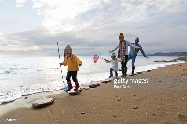 Family walking on stepping stones on beach
