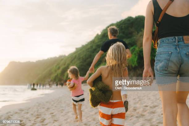 family  walking on the beach in bali - tropical climate stock photos and pictures