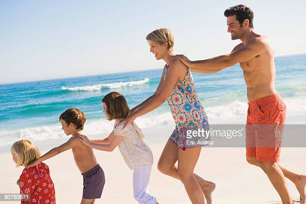 Family walking on the beach in train formation