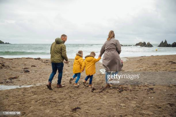family walking on the beach - back stock pictures, royalty-free photos & images