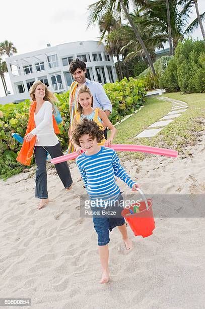 Family walking on the beach with a tourist resort in the background