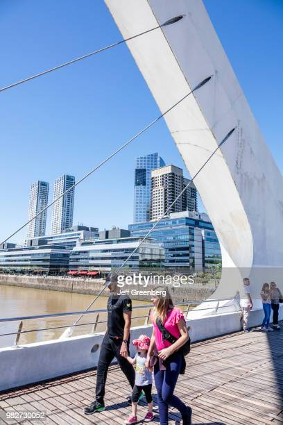 A family walking on the Puente De La Mujer pedestrian suspension swing bridge