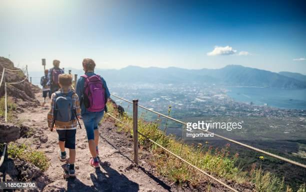 family walking on the summit of mount vesuvius volcano in campania, italy. - guardare il paesaggio foto e immagini stock