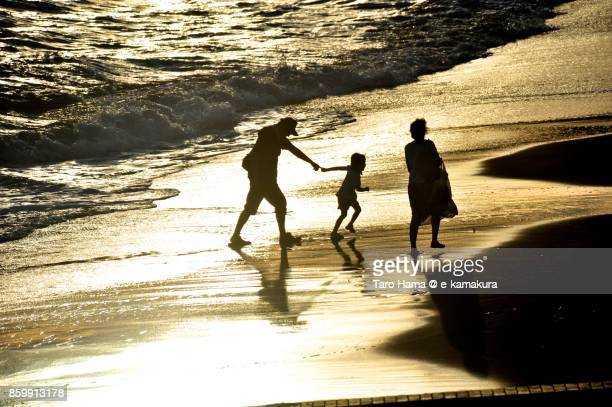 A family walking on the sunset beach in Kamakura city in Kanagawa prefecture in Japan
