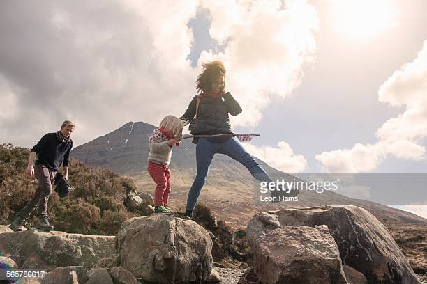 Family walking over boulders, Fair Pools, Isle of Skye, Hebrides, Scotland