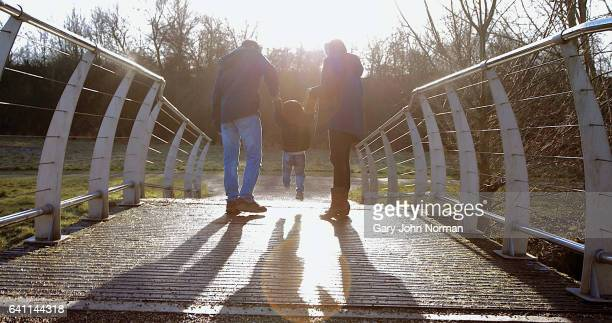 family walking over bridge in park, swinging young son between them. - milton keynes stock pictures, royalty-free photos & images
