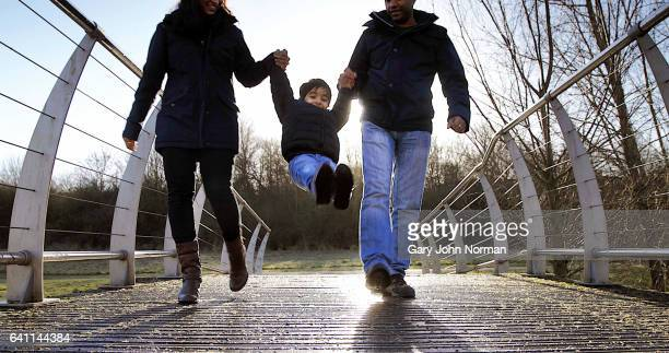 family walking over bridge in park, swinging young son between them. - milton keynes stock photos and pictures