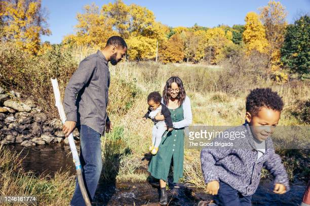 family walking over stream in countryside - crossing stock pictures, royalty-free photos & images