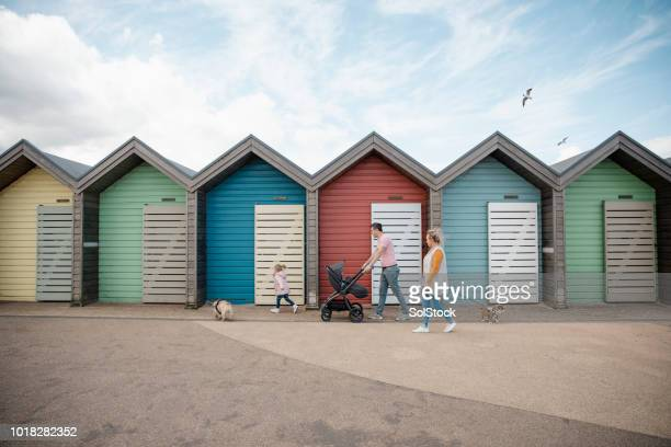 family walking past colourful beach huts - northumberland stock photos and pictures