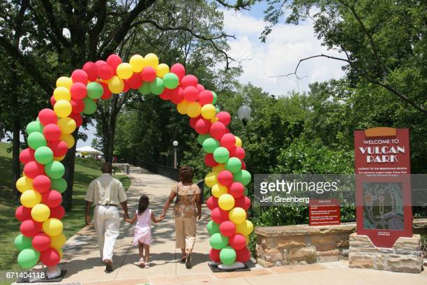 A family walking through an archway of balloons into Vulcan Park