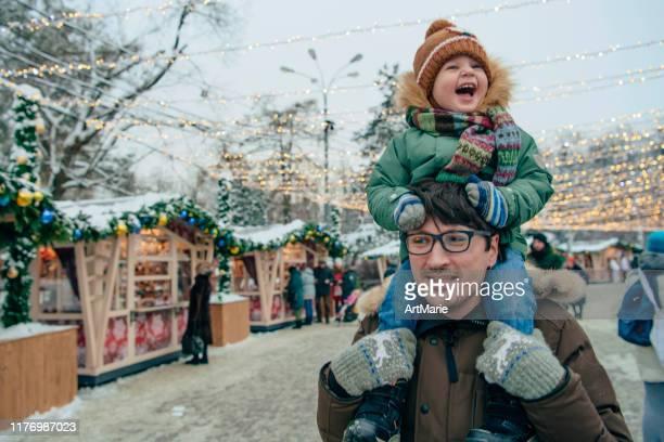 família que anda através do mercado do natal - mercado natalino - fotografias e filmes do acervo