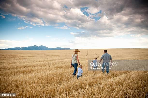 family walking through cut wheat field