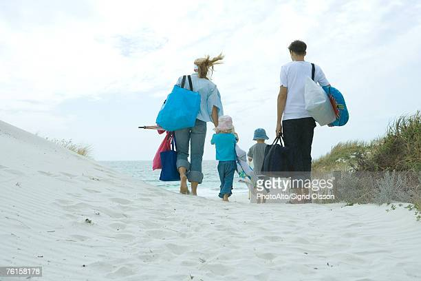 family walking through dunes to beach - woman carrying tote bag stock photos and pictures