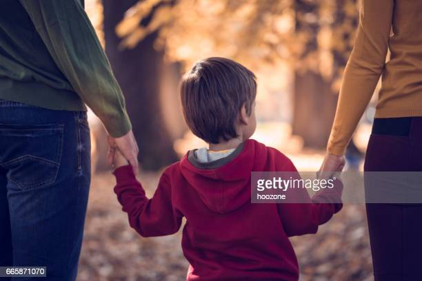 family walking through leaves in nature - family with one child stock pictures, royalty-free photos & images