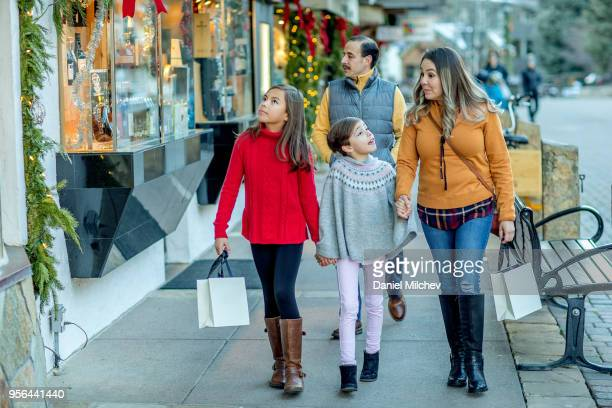 family walking through mountain town with shopping bags, browsing stores. - lane sisters stock photos and pictures