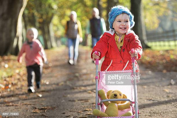 family walking through park in autumn - pushchair stock pictures, royalty-free photos & images