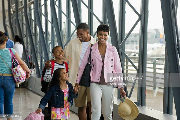 family walking together in airport - kid in airport stock pictures, royalty-free photos & images