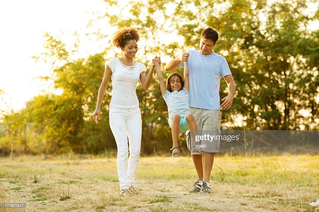 Family walking together in field at sunset : Stock Photo