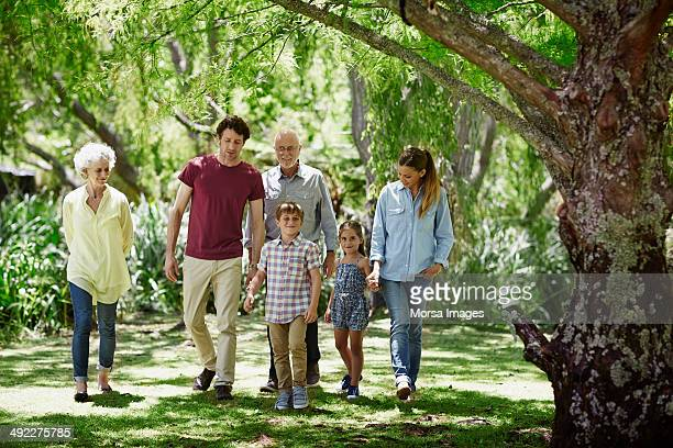 family walking together in park - multigenerational family stock pictures, royalty-free photos & images