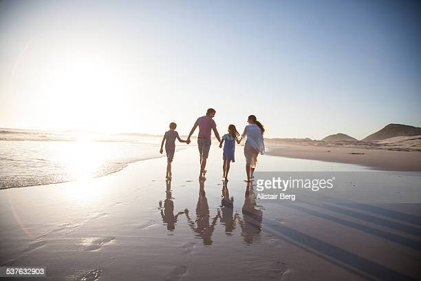 family walking together on a beach - holiday stock pictures, royalty-free photos & images