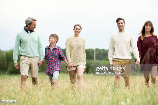 family walking together through field of tall grass - さまざまな年齢層 ストックフォトと画像
