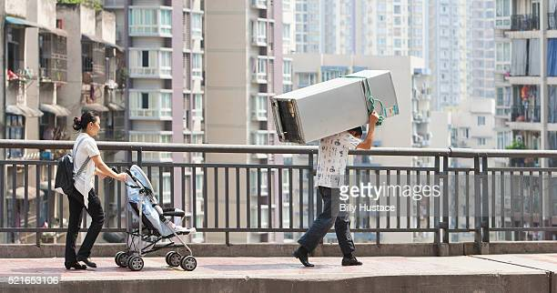 A family walking together, with the father carrying a large appliance on his back in an Asian city