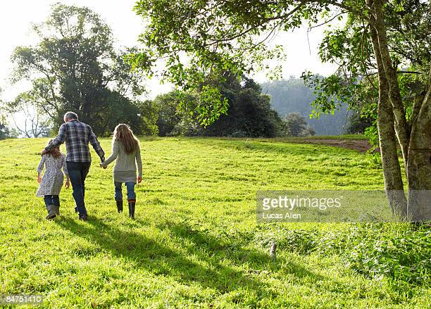 family walking up a grassy hill together  - landelijke scène stockfoto's en -beelden
