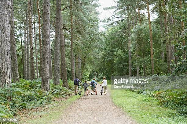 Family walking with bicycles in woods