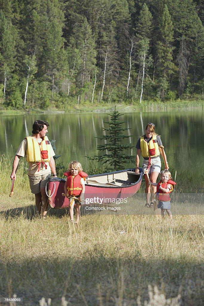 Family walking with canoe : Stockfoto