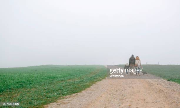 Family walking with dog on a path on a foggy winter day