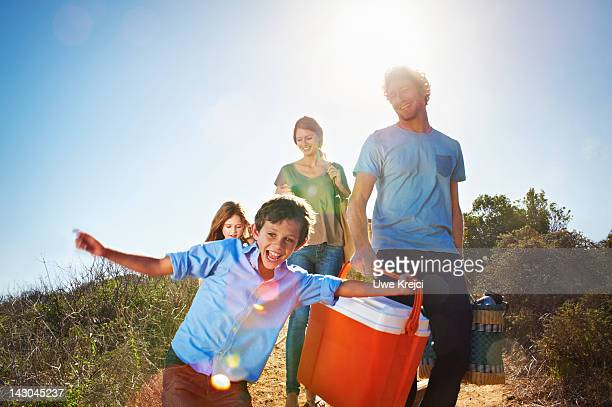 family walking with picnic paraphernalia in park - picnic stock pictures, royalty-free photos & images