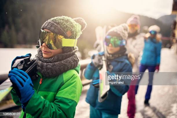 family walking with skis on sunny winter day - ski holiday stock photos and pictures