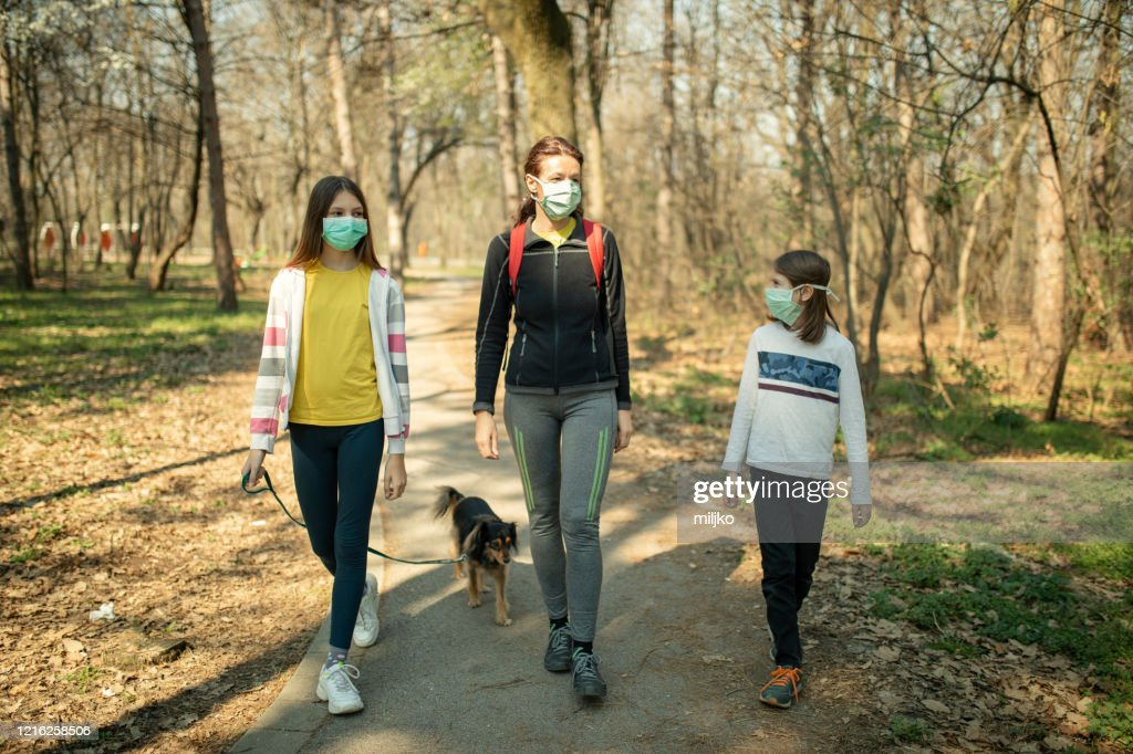Family walking with their dog in park and wearing mask : Stock Photo