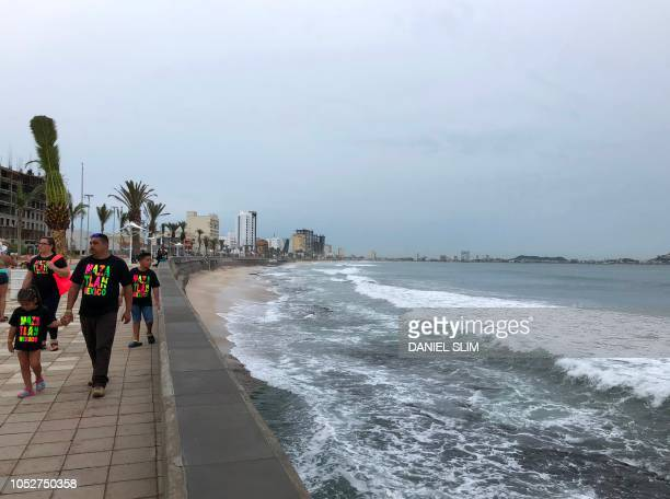 A family walks along teh coastline in Mazatlan Sinaloa state Mexico on October 22 before the arrival of Hurricane Willa Hurricane Willa upgraded to...