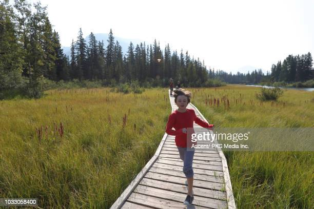 family walks along wooden boardwalk, above marsh - pedal pushers stock pictures, royalty-free photos & images
