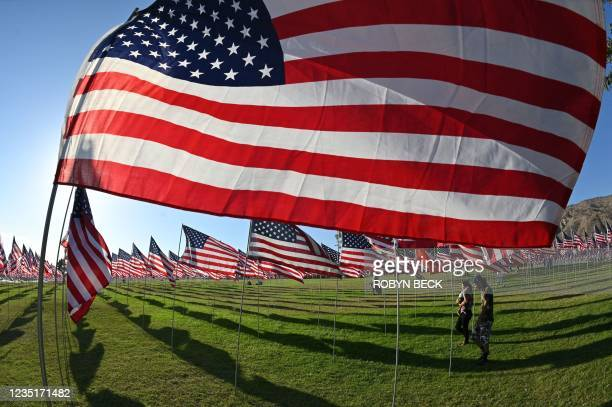 Family walks among American flags displayed to commemorate lives lost in the 9/11 terror attack, on September 10, 2021 at Pepperdine University in...