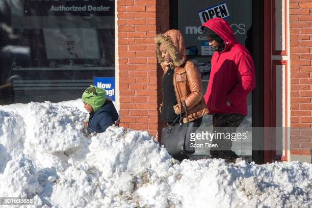 A family walks amongst large snowpiles the day after the region was hit with a 'bomb cyclone' on January 5 2018 in the Dorchester neighborhood of...