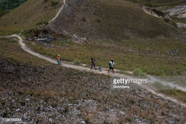 Family walks back from a well after fetching water near the Venezuelan border in Pacaraima, Brazil, on Wednesday, April 10, 2019. Venezuelan refugees...