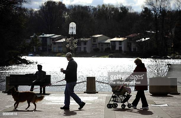 A family walks by a bronze sculpture of Robert Simon at Lake Anne Village in Reston The sulpture entitled 'Untold Stories' was crafted by Zachary...