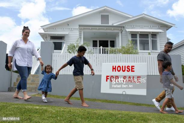 family walks in front of a home for sale - rafael ben ari stockfoto's en -beelden