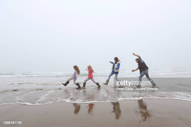 family walks on stepping stones along shoreline - stepping stock pictures, royalty-free photos & images