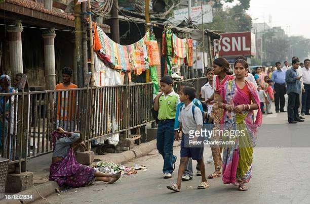 A family walks past a beggar on a Kolkata street